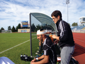 Tyler Ker fixes makeshift headgear for Justin Sekhon after the midfielder took an elbow to the crown.