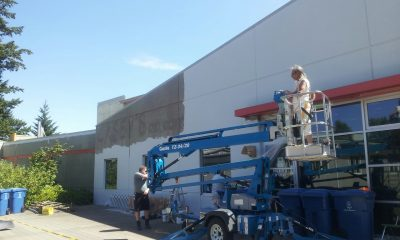 Old aftermath space exterior being painted white by crews